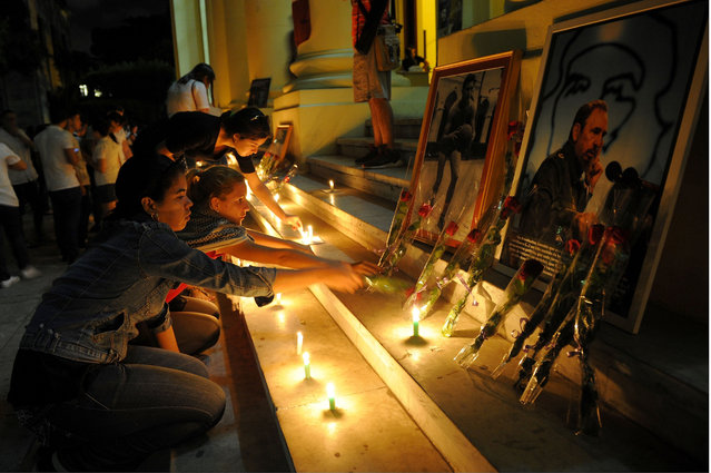 Students light candles in honour of Cuban historic revolutionary leader Fidel Castro a day after his death, at the Havana University in Havana on November 26, 2016. Cuban revolutionary icon Fidel Castro died late Friday in Havana, his brother, President Raul Castro, announced on national television. Castro's ashes will be buried in the historic southeastern city of Santiago on December 4 after a four-day procession through the country. (Photo by Yamil Lage/AFP Photo)