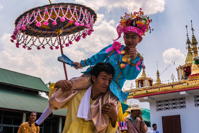 An initiate nearly takes a tumble atop his father's shoulder during the parade in Mae Hong Son, Thailand, April 2016. (Photo by Claudio Sieber/Barcroft Images)