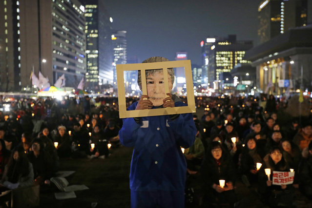 A protester wearing a mask of South Korean President Park Geun-hye performs during a rally calling for Park to step down in Seoul, South Korea, Wednesday, November 30, 2016. South Korean President Park Geun-hye's conditional resignation offer appears to be causing cracks in what previously had been a strong push for her impeachment, with opponents now struggling to set a date for a vote to strip her of power. (Photo by Ahn Young-joon/AP Photo)