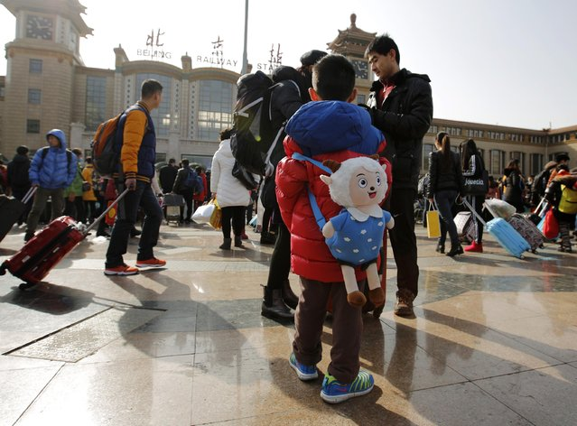 A boy carries a backpack in the shape of Xiyangyang, a cartoon character also known as Pleasant Goat, at a railway station in Beijing February 16, 2015. (Photo by Kim Kyung-Hoon/Reuters)