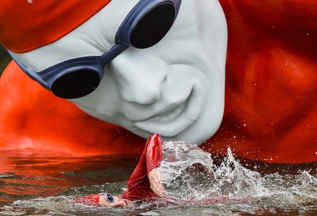 A swimmer passes a temporary floating sculpture as he trains on the Serpentine Lake at Hyde Park in London, on September 11, 2013. Ennis-Hill launched the upcoming World Triathlon Grand Final which takes place this weekend. (Photo by Toby Melville/Reuters)