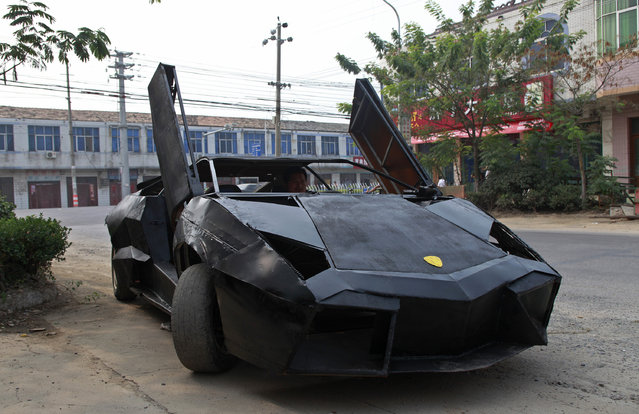 A friend of Wang Jian sits in a hand-made replica of a Lamborghini Reventon in Suqian, Jiangsu province August 30, 2012. Wang, a young Chinese farmer who worked at a garage for more than a decade, built the replica of a Lamborghini Reventon with a second-hand Nissan and Santana. The self-made roadster cost Wang around 60,000 RMB ($9,450) and can reach a maximum speed of 160mph, according to local media reports. (Photo by Reuters/Xihao)