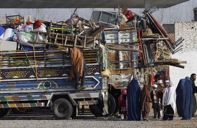 An Afghan refugee family stands by trucks loaded with their belongings as they wait to go back to Afghanistan with others, at the United Nations High Commissioner for Refugees (UNHCR) office on the outskirts of Peshawar February 13, 2015. (Photo by Fayaz Aziz/Reuters)