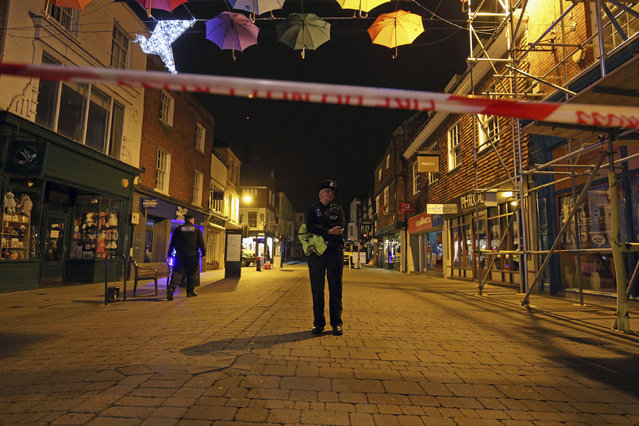"A police officer stands behind a cordon on the High Street in Salisbury, Britain, where police closed roads as a ""precautionary measure"" after two people were taken ill from the Prezzo restaurant, right in the background, Sunday, September 16, 2018. Police closed roads and called a hazardous response team Sunday night after two people became ill at the restaurant in the English city where a Russian ex-spy and his daughter were poisoned with a chemical nerve agent. The conditions of a man and woman who got sick at the restaurant was under investigation. (Photo by Jonathan Brady/PA Wire via AP Photo)"