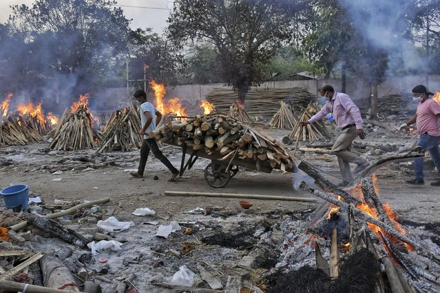 A worker carries wood on a hand cart as multiple funeral pyres of COVID-19 victims burn at a crematorium on the outskirts of New Delhi, India, Saturday, May 1, 2021. India on Saturday set yet another daily global record with 401,993 new cases, taking its tally to more than 19.1 million. Another 3,523 people died in the past 24 hours, raising the overall fatalities to 211,853, according to the Health Ministry. Experts believe both figures are an undercount. (Photo by Ishant Chauhan/AP Photo)