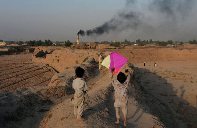 This photograph taken on October 18, 2016 shows Afghan youths playing with a kite on the outskirts of Jalalabad. (Photo by Noorullah Shirzada/AFP Photo)
