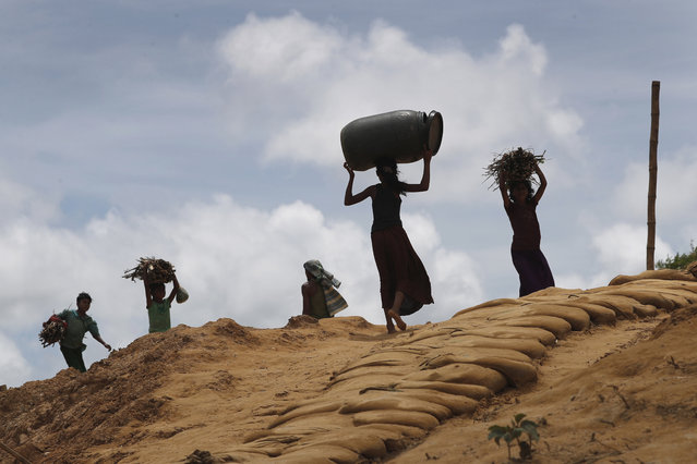 Rohingya girls carry firewood on their heads as they make their way through Kutupalong refugee camp, Thursday, June 28, 2018, in Bangladesh. (Photo by Wong Maye-E/AP Photo)