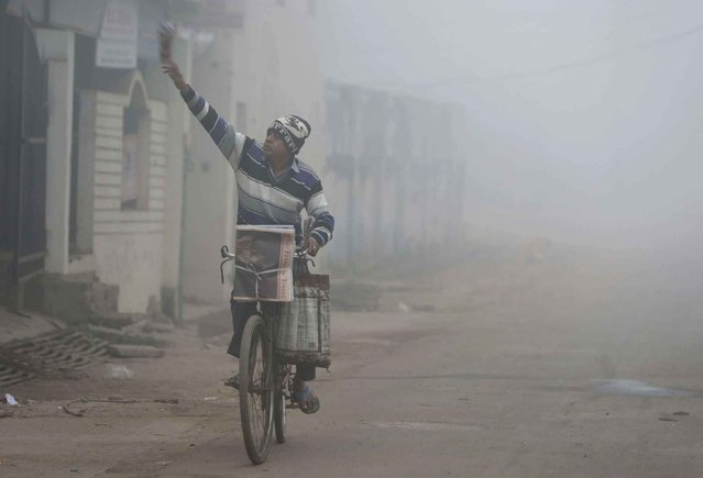 A newspaper vendor distributes newspapers to different houses on a foggy morning in Allahabad, India, Tuesday, December 6, 2016. In the winter months, northern India experiences fog enveloped mornings that reduce visibility severely, often leading to delays and cancellation of trains and flights. (Photo by Rajesh Kumar Singh/AP Photo)