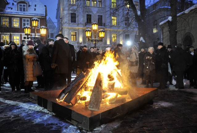 Latvians gather at a bonfire marking the 25th anniversary of a Soviet crackdown on pro-independence protesters, at the  Parliament building, in Riga, Latvia, Wednesday, January 20, 2016. Latvia marked  the 25th anniversary of a Soviet crackdown as the country strived for independence. (Photo by Roman Koksarov/F64 via AP Photo)