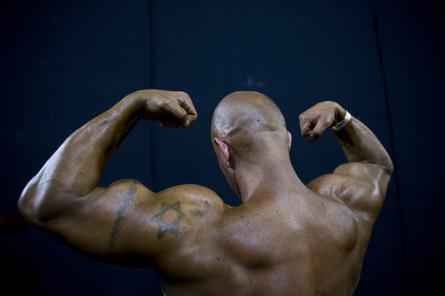 In this Thursday, October 18, 2018 photo, a contestant exercises backstage during the National Amateur Body Builders' Association competition in Tel Aviv, Israel. Exhausted from weeks of strict dieting and last-minute exertions, the muscle-bound athletes primped, painted and prepped before taking the stage. (Photo by Oded Balilty/AP Photo)