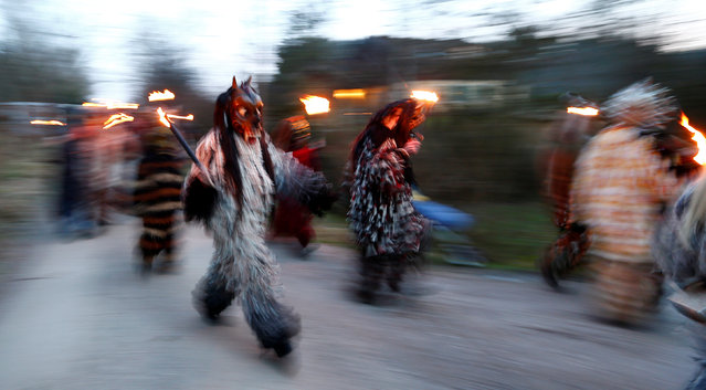 Costumed participants perform during a traditional Perchtenlauf (Perchten parade) in Osterseeon near Munich, Germany, December 17, 2016. (Photo by Michaela Rehle/Reuters)