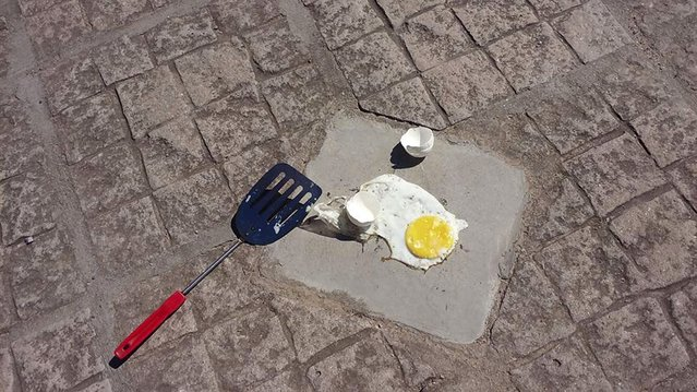 View of an egg fried on the pavement in Pozo Hondo, Santiago del Estero, Argentina on January 23, 2016, while the real feel was 57 degrees Celsius. Pozo Hondo's Mayor Claudio Nicolau fried an egg on the pavement of the main square of the city Saturday. (Photo by AFP Photo/Stringer)