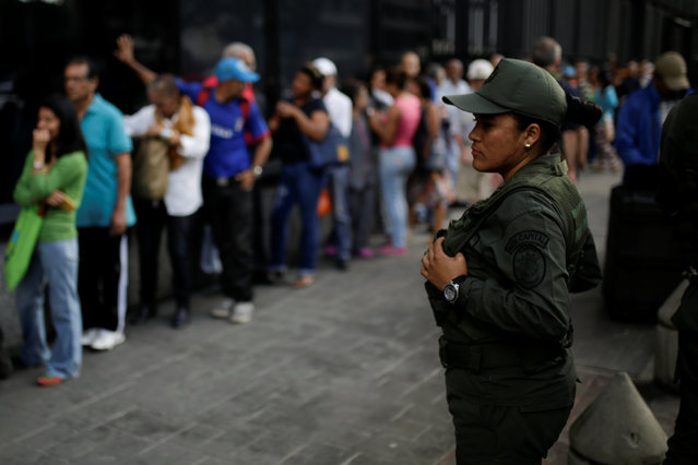 A Venezuelan soldier stands guard as people line up to get into a Banco Mercantil branch in Caracas, Venezuela December 13, 2016. (Photo by Marco Bello/Reuters)