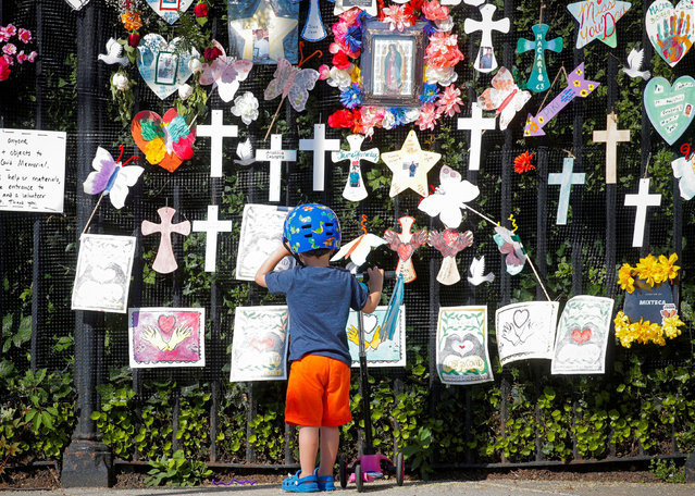 """A child looks at the """"Naming the Lost Memorials"""", as the U.S. deaths from the coronavirus disease (COVID-19) are expected to surpass 600,000, at The Green-Wood Cemetery in Brooklyn, New York, U.S., June 10, 2021. (Photo by Brendan McDermid/Reuters)"""