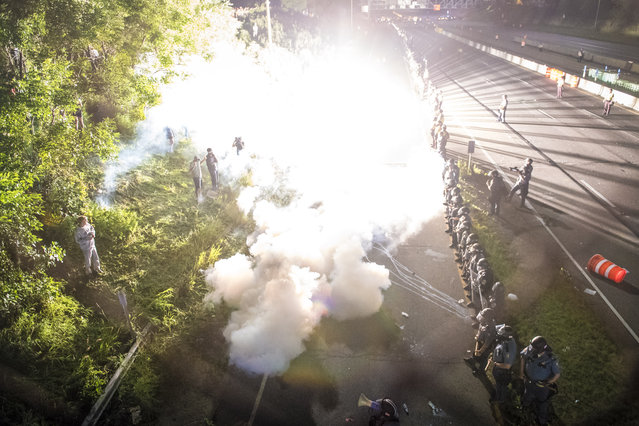 Officers shoot gas, stun grenades, and pepper spray at demonstrators blocking I-94 near the Dale St. exit during a protest for Philando Castile in Falcon Heights, Minn. on Saturday July 09, 2016. Philando Castile was shot and killed after a traffic stop by police in Falcon Heights, Wednesday night. A video shot by Diamond Reynolds of the shooting went viral. (Photo by Jabin Botsford/The Washington Post)