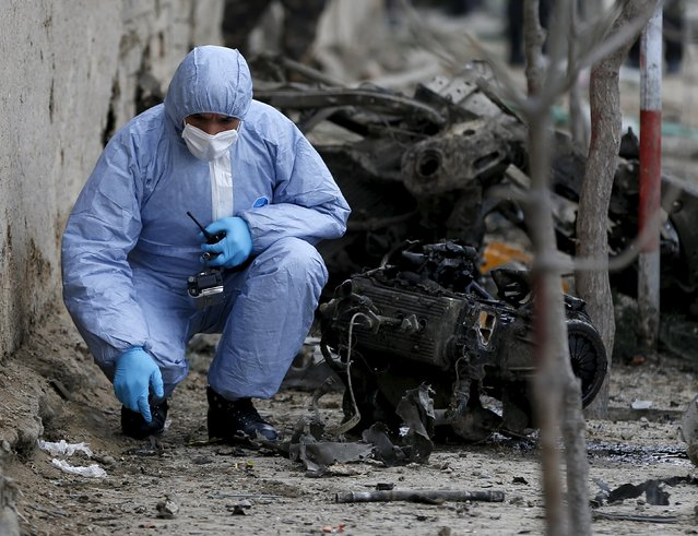 A member of the Afghan security forces investigates at the site of a suicide attack in Kabul March 25, 2015. (Photo by Omar Sobhani/Reuters)