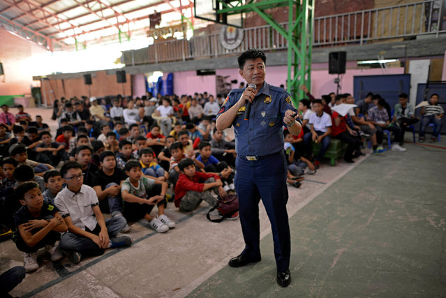 """Police officer Ronaldo David, 49, speaks during a drug awareness seminar for school children in Pasay city, Metro Manila, Philippines October 1, 2016. """"My load in filing cases in the office has been reduced. I am now more focused on educating people and in prevention"""", he said. (Photo by Ezra Acayan/Reuters)"""