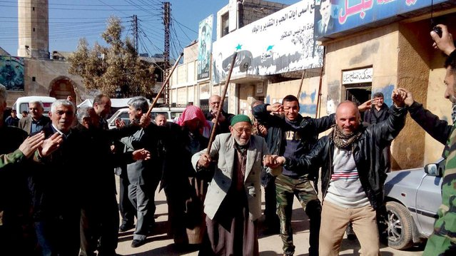 Residents of Nubul and al-Zahraa, along with forces loyal to Syria's President Bashar al-Assad, celebrate after the siege of their towns was broken, northern Aleppo countryside, Syria, in this handout picture provided by SANA on February 4, 2016. (Photo by Reuters/SANA)