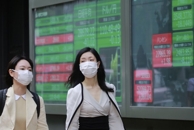 People walk by an electronic stock board of a securities firm in Tokyo, Wednesday, July 14, 2021. (Photo by Koji Sasahara/AP Photo)