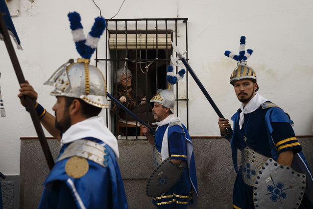 "An old woman looks from her house window as penitents dressed as Roman empire soldiers take part in ""Nuestro Senor Atado a la Columna, Maria Santisima de la Paz y San Juan Evangelista"" Holy Week procession in Arcos de la Frontera, Spain, Tuesday, March 31, 2015. (Photo by Daniel Ochoa de Olza/AP Photo)"