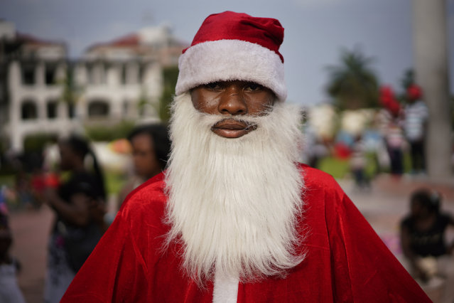 A Congolese Santa Claus waits to pose with children in Kinshasa, Congo, Tuesday Decenber 25, 2018. Traditionally Congolese dress up and take to the parks on Christmas day, this time five days before scheduled presidential and general elections. (Photo by Jerome Delay/AP Photo)