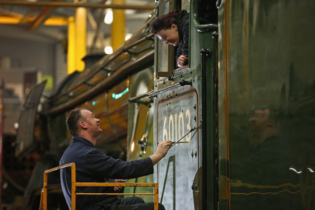 Heritage painter Mike O'Connor paints engine number 60103 onto the side of the Flying Scotsmans cab, watched by his daughter, Teriann O'Connor, aged 21, who is part of the Heritage painting team at the National Railway Museum in York, ahead of its official return to steam next week. February 17, 2016 in York, England. (Photo by Christopher Furlong/Getty Images)