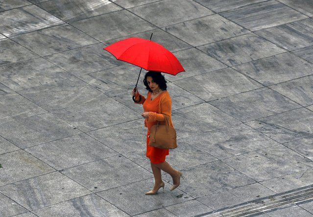 A woman walks through Athens' Syntagma (Constitution) square during a rainy Spring day March 26, 2015. (Photo by Yannis Behrakis/Reuters)