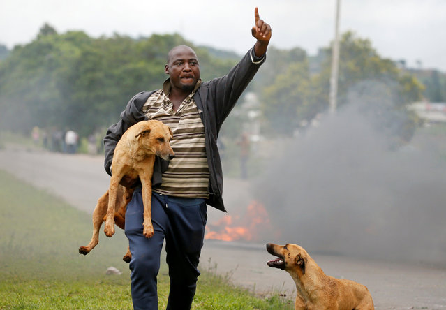 A protester gestures as he holds a dog before a burning barricade during protests in Harare, Zimbabwe, January 15, 2019. (Photo by Philimon Bulawayo/Reuters)