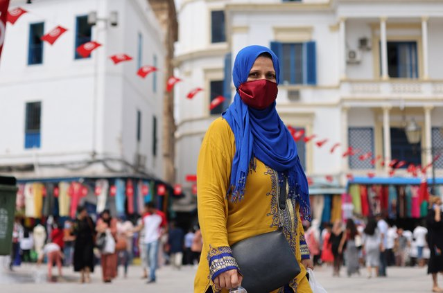 A woman wearing protective face mask walks while shopping, amid the coronavirus disease (COVID-19) outbreak, in the Old City of Tunis, Tunisia, August 3, 2021. (Photo by Ammar Awad/Reuters)