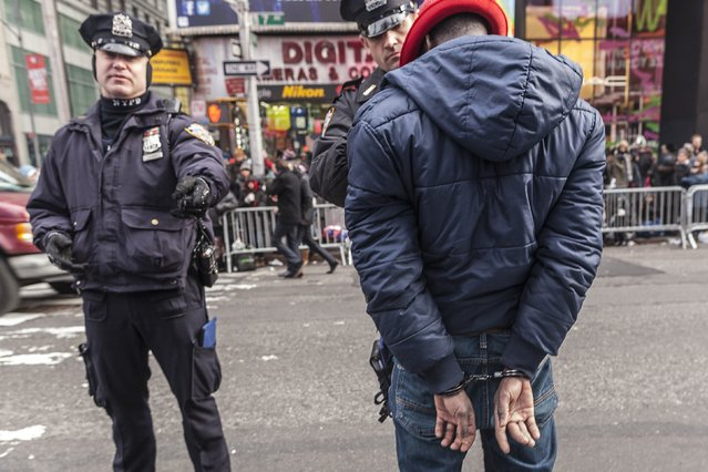 A man is hand-cuffed by the New York Police Department before New Year's Eve celebrations in Times Square in New York, December 31, 2013. (Photo by Zoran Milich/Reuters)