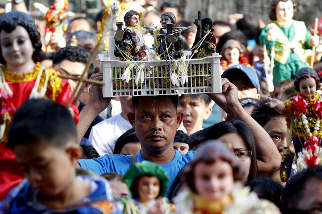 In this Sunday, January 20, 2019, file photo, Roman Catholic devotees raise hundreds of images of the Child Jesus, known as Santo Niño, as they are blessed with holy water to celebrate its feast da, in Manila, Philippines. Many parishes around the country whose patron saint is the Child Jesus take part in the celebration which culminates in a mass and procession. (Photo by Bullit Marquez/AP Photo)