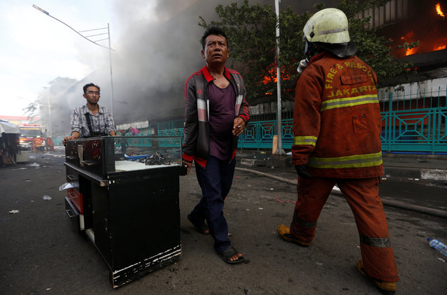 People move their belongings and goods during a large fire at Senen market in Jakarta, Indonesia January 19, 2017. (Photo by Darren Whiteside/Reuters)