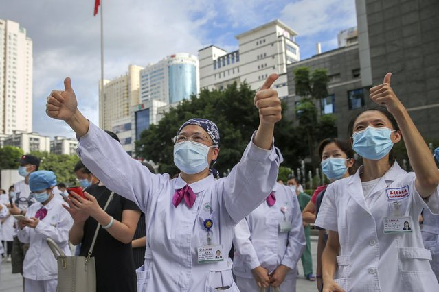 Medical workers give thumbs-up to their colleagues leaving to help with an outbreak of COVID-19 in Putian from a provincial hospital in Fuzhou in southeast China's Fujian province Sunday, September 12, 2021. Putian, a city in southern China that is trying to contain a coronavirus outbreak told the public Sunday not to leave, suspended bus and train service and closed cinemas, bars and other facilities. (Photo by Chinatopix via AP Photo)