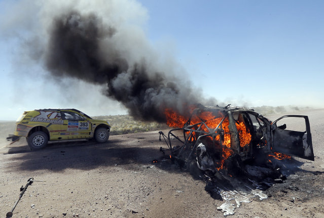 Chile's Javier Campillay drives past the burning car of Kazakhstan's Bauyrzhan Issabayev and Gabdulla Ashimov during the Dakar Rally 2014 Stage 2 from San Luis to San Rafael, on January 6, 2014. (Photo by Jean-Paul Pelissier/AFP Photo)