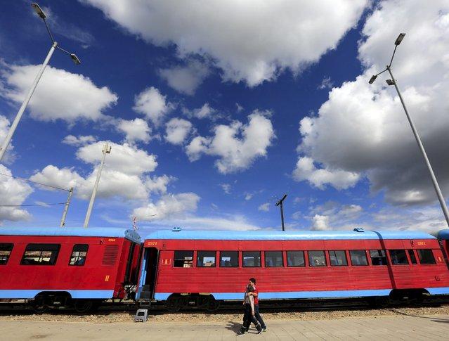 "A couple walk close to a ""La Sabana"" tourist train in Cajica city March 1, 2015. (Photo by Jose Miguel Gomez/Reuters)"