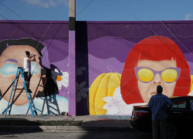 Winston Farrar helps paint a mural by artist, Cloe Hakakian, on the side of a building, as the Wynwood neighborhood prepares for the annual Art Basel art fair on December 03, 2018 in Miami, Florida. Artists and art lovers from around the world flock to the Miami area from Dec. 6 to the 9th to visit Art Basel as well as the satellite galleries that pop up throughout the city during the week. (Photo by Joe Raedle/Getty Images)