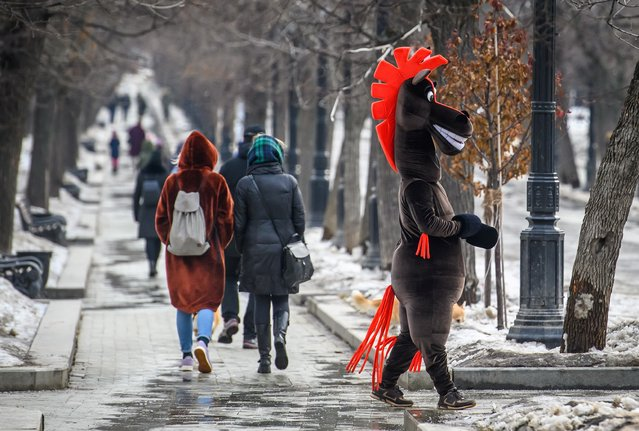 A man dressed as a horse entertains pedestrians on a boulevard in Central Moscow on March 15, 2019. (Photo by Mladen Antonov/AFP Photo)