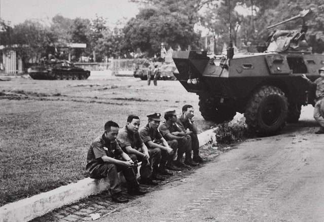 South Vietnamese officers sit dejectedly on a curb outside the Presidential Palace shortly after North Vietnamese troops captured the Palace in Saigon, ending the Vietnam war on April 30, 1975 in this photo taken by North Vietnamese photograper Dinh Quang Thanh. Nam's images taken as he arrived with the North Vietnamese troops captured a mood different from many of the most familiar photos by western photographers, whose images showed the scenes of panic in the final hours of the war. (Photo by Dinh Quang Thanh/AP Photo/Vietnam News Agency)