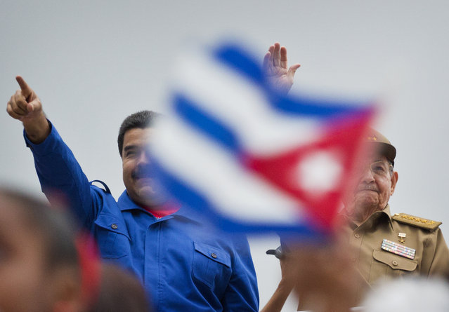 Venezuela's President Nicolas Maduro, left, and Cuba' President Raul Castro acknowledge marchers as they parade past marking May Day in Revolution Square, in Havana, Cuba, Friday, May 1, 2015. (Photo by Ramon Espinosa/AP Photo)