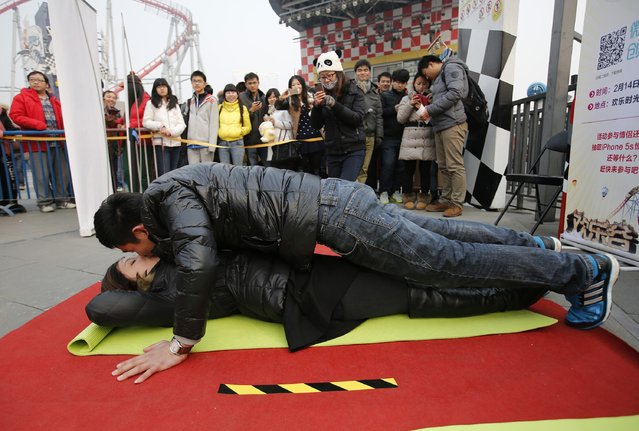 A couple kisses, as the man does push-ups, during a kissing contest held in celebration of Valentine's Day at the Happy Valley amusement park in Beijing February 14, 2014. About 100 couples competed by kissing in various poses during the competition and an iPhone 5S was presented to the winning couple. (Photo by Kim Kyung-Hoon/Reuters)