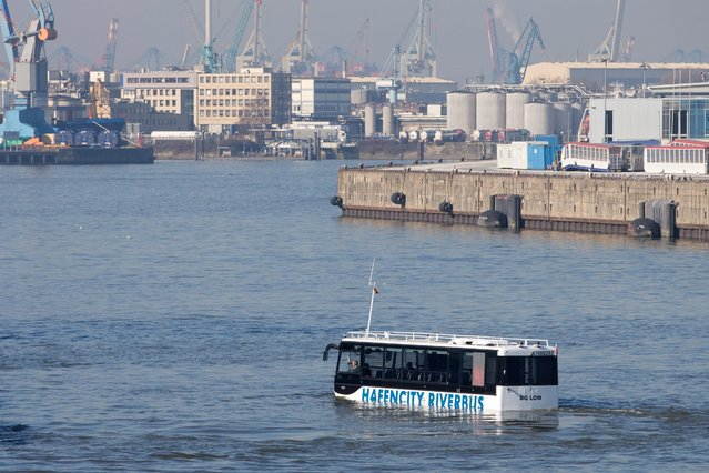 "An amphibious bus swimming through the HafenCity quarter in Hamburg, Germany, 17 March 2016. The new ""HafenCity RiverBus"" is said to combine city and harbour tours for tourists from April onwards. (Photo by Christian Charisius/EPA)"