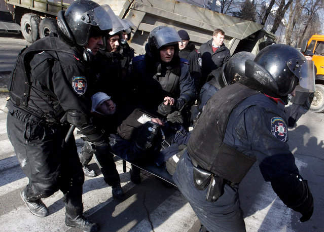 Policemen carry a colleague wounded during clashes with anti-government protesters in Kiev on February 18, 2014. (Photo by Yury Kirnichny/AFP Photo)