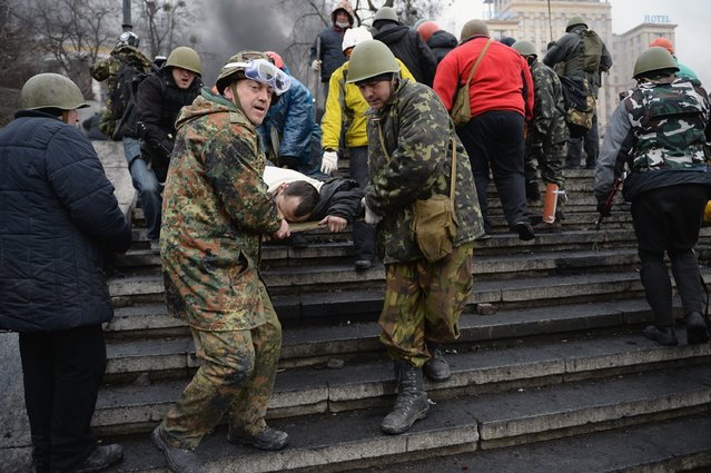Anti-government protesters carry the injured during continued clashes with police in Independence square, despite a truce agreed between the Ukrainian president and opposition leaders on February 20, 2014 in Kiev, Ukraine. (Photo by Jeff J. Mitchell/Getty Images)