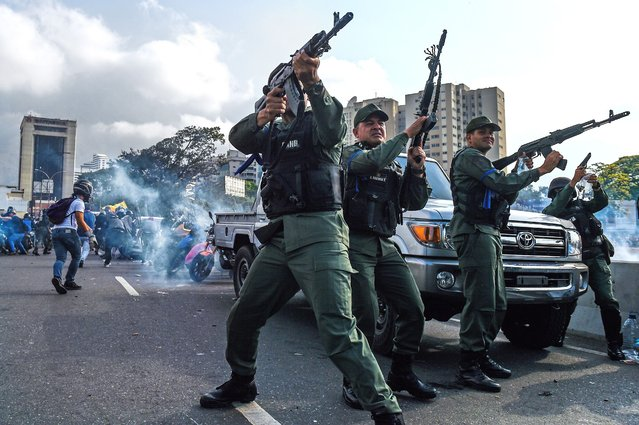 "Members of the Bolivarian National Guard who joined Venezuelan opposition leader and self-proclaimed acting president Juan Guaido fire into the air to repel forces loyal to President Nicolas Maduro who arrived to disperse a demonstration near La Carlota military base in Caracas on April 30, 2019. Guaido – accused by the government of attempting a coup Tuesday – said there was ""no turning back"" in his attempt to oust President Nicolas Maduro from power. (Photo by Federico Parra/AFP Photo)"
