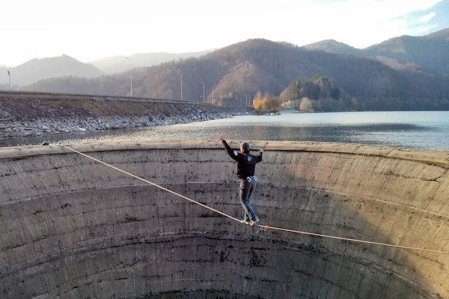 Daredevil Flaviu Cernescu, 31, walks on a slack-line over a reservoir drain in Lake Iovanu, Romania. (Photo by Flaviu Cernescu / Barcroft Media)