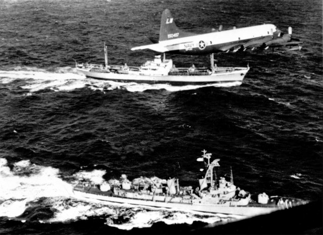 The U.S. destroyer Barry pulls alongside the Russian freighter Anosov in the Atlantic Ocean, November 10, 1962, to inspect cargo as a U.S. patrol plane flies overhead. The Soviet ship presumably carries a cargo of missiles being withdrawn from Cuba. The interception took place about 780 miles northeast of Puerto Rico. (Photo by AP Photo)