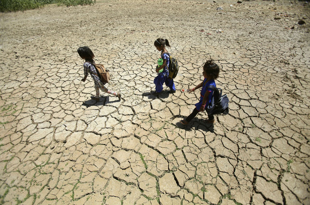 In this Thursday, May 30, 2019, file photo, children returning from school walk through a dried pond on a hot summer day on the outskirts of Jammu, India. Many parts of India are experiencing extreme heat conditions. (Photo by Channi Anand/AP Photo/File)