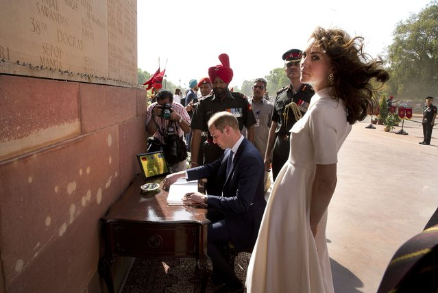 Britain's Prince William, signs visitor's book  as his wife Kate, the Duchess of Cambridge looks on after paying their tributes at the India Gate war memorial, in the memory of the soldiers from Indian regiments who served in World War I, in New Delhi, India, Monday, April 11, 2016. (Photo by Manish Swarup/Pool Photo via AP Photo)