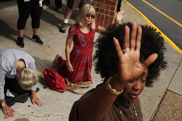 (L-R) Cathy Whitley, Brenda Flowers and Renee Gathers pray during a service organized by Lifehouse Virginia Beach in the parking lot of a local shopping center the day after a mass shooting left 13 people dead June 01, 2019 in Virginia Beach, Virginia. The names of the 12 victims of Friday's shooting rampage at the city's Municipal Center were made public along with the identity of the shooter, city engineer DeWayne Craddock. (Photo by Chip Somodevilla/Getty Images)