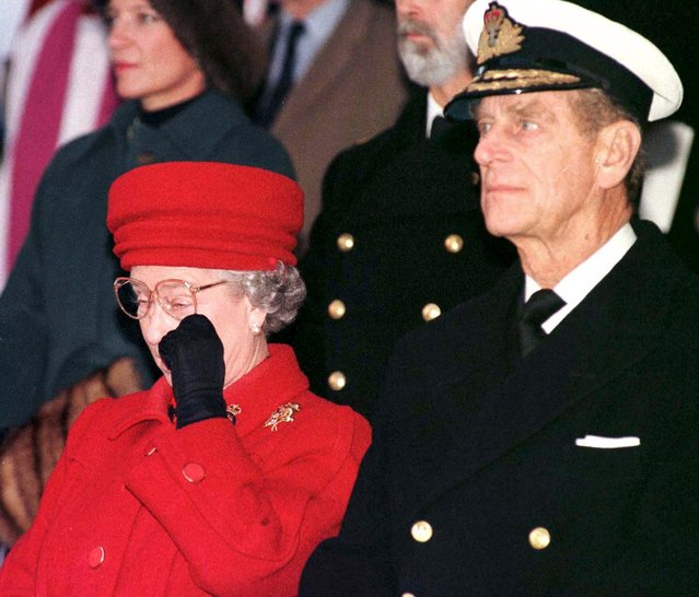 Britain's Queen Elizabeth accompanied by her husband Prince Philip, wipes away a tear during the formal decommissioning service for the Royal yacht HMS Britannia at Portsmouth harbour, Britain, in this December 11, 1997 file photo. (Photo by Reuters/Stringer)